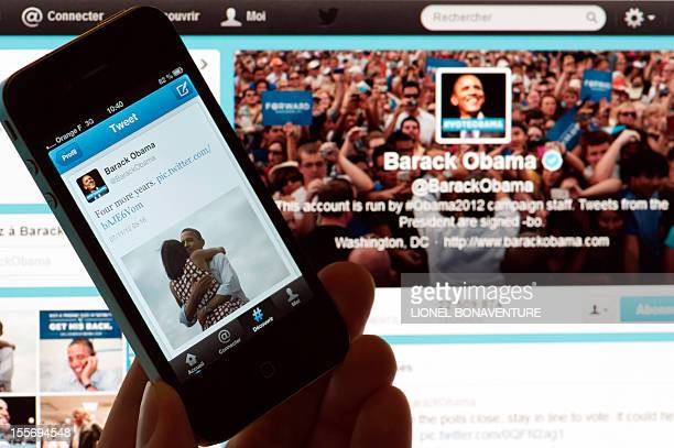 A person poses with a cell phone in front of a computer screen to check Barack Obama's tweet on November 7 2012 in Paris after his reelection as US...