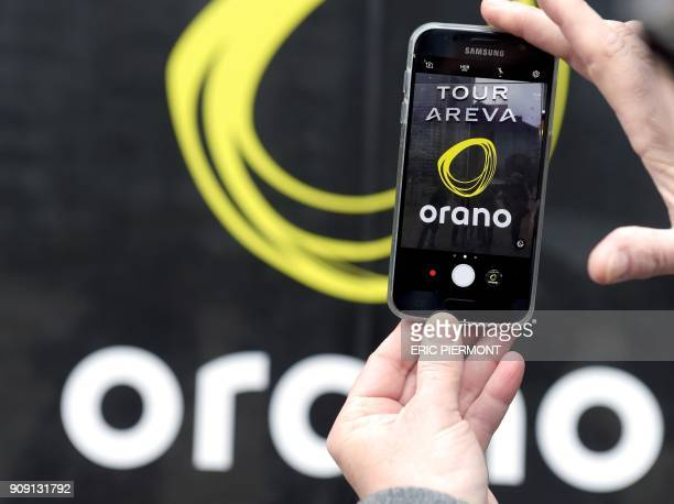 A person poses with a cell phone in front of the logo of Orano the new brand name of Areva in front of the headquarters in La Defense business...