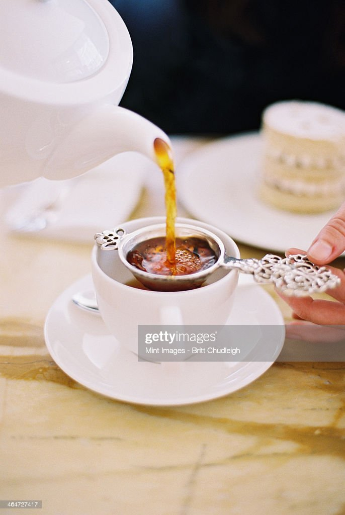 A person pouring a cup of tea, using a strainer. White china. Elegant afternoon tea. : Stock Photo