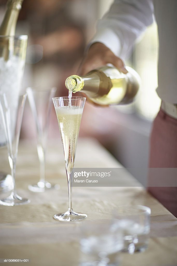 Person pouring champagne into glass, close-up, Mid section : Stockfoto
