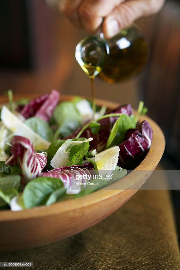 Person pouring oil onto salad in wooden bowl, close-up : Stockfoto