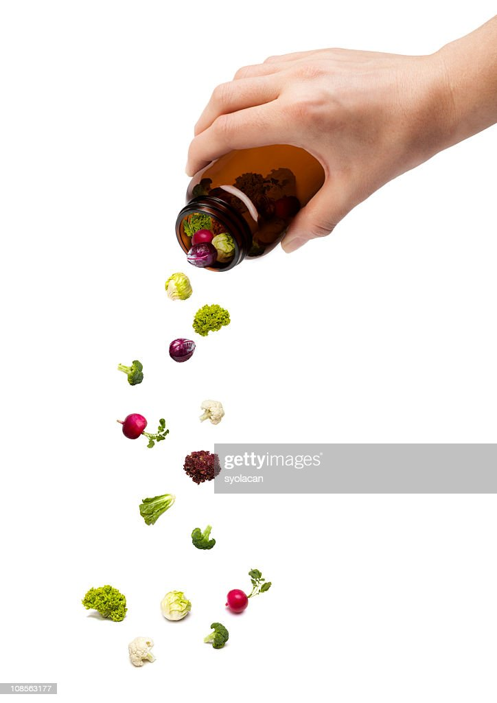 A person pouring out a pill jar with tiny vegetables : Stock Photo