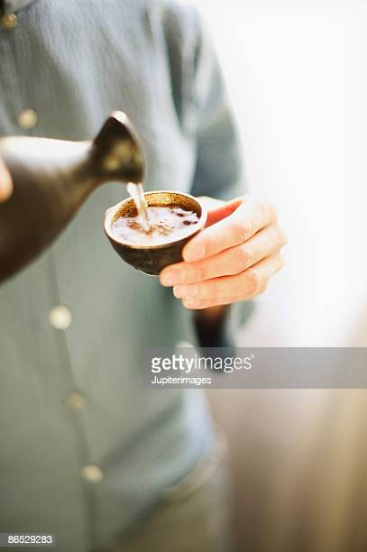 person pouring sake into cup - saki stock photos and pictures