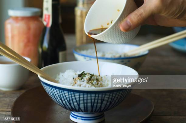 person pouring sauce over bowl of rice - soy sauce stock photos and pictures