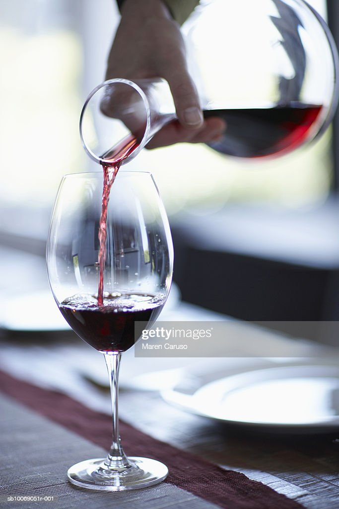 Person pouring wine from decanter into wine glass, close-up : Stockfoto