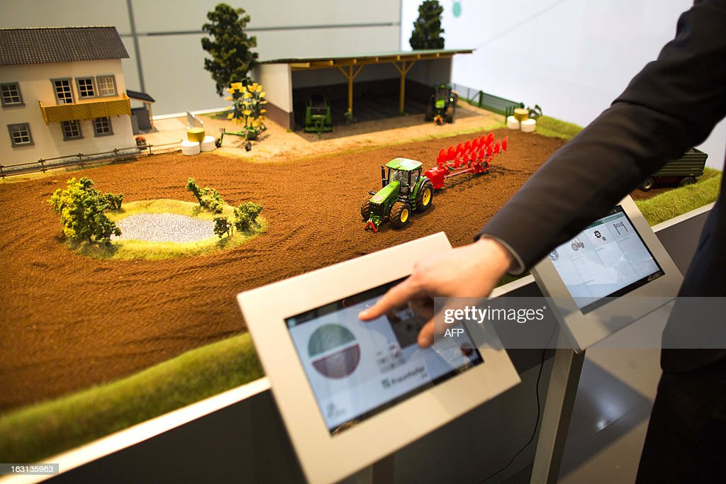 A person presents models of electronically controlled tractors during a demonstration at Fraunhofer institute stand at the 2013 CeBIT technology trade fair on March 5, 2013 in Hanover, Germany. CeBIT will be open March 5-9.