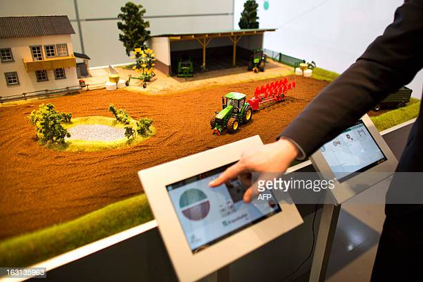 Person presents models of electronically controlled tractors during a demonstration at Fraunhofer institute stand at the 2013 CeBIT technology trade...