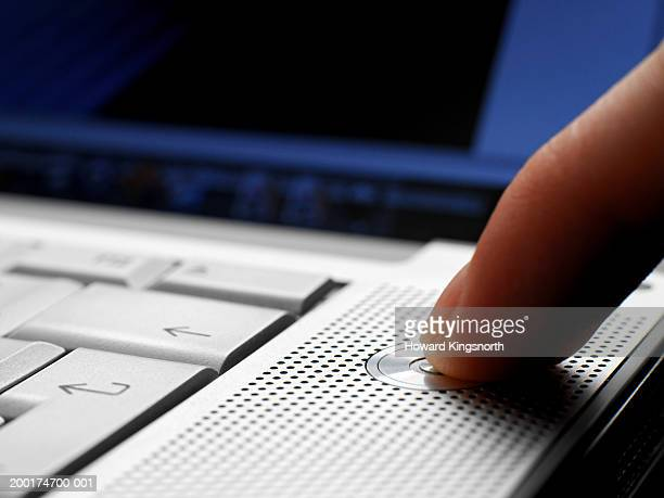 Person pressing power button on laptop computer, close-up
