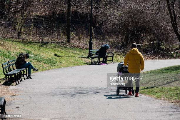 Person pushes a baby carriage through Prospect Park in the Brooklyn borough of New York, U.S., on Thursday, March 26, 2020. New York Governor Andrew...