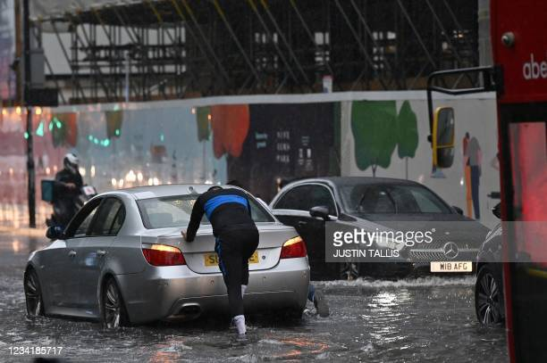 Person pushes a broken-down car through deep water on a flooded road in The Nine Elms district of London on July 25, 2021 during heavy rain. - Buses...