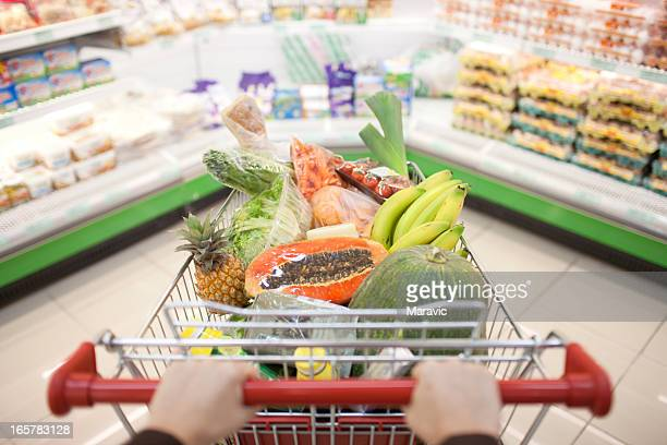 A person pushing a cart full of fruit at the store