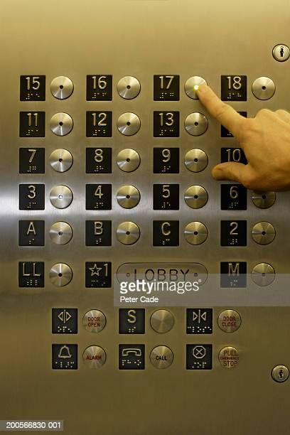 Person pushing button on panel in elevator, close-up