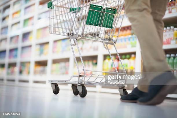 pessoa que empurra o carro de compra no corredor do supermercado - mercado espaço de venda no varejo - fotografias e filmes do acervo