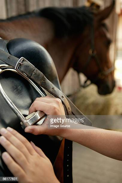 Person putting a saddle on a horse