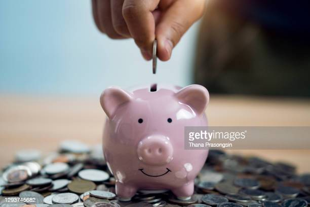 person putting coin in piggy bank at table - piggy bank stock pictures, royalty-free photos & images