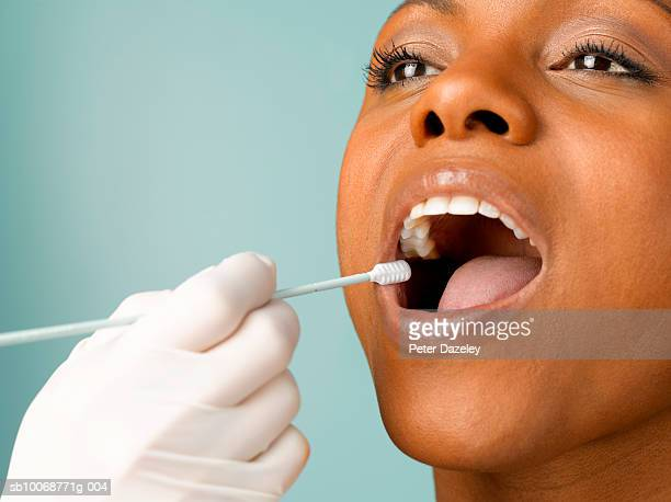 Person putting DNA test swab into woman's mouth, close up, studio shot