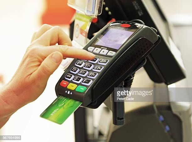 person putting in pin number in card machine .