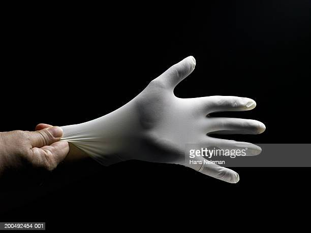 Person putting on white surgical glove, close-up of hand, side view