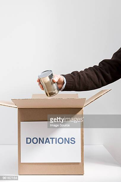 Person putting tin in donation box