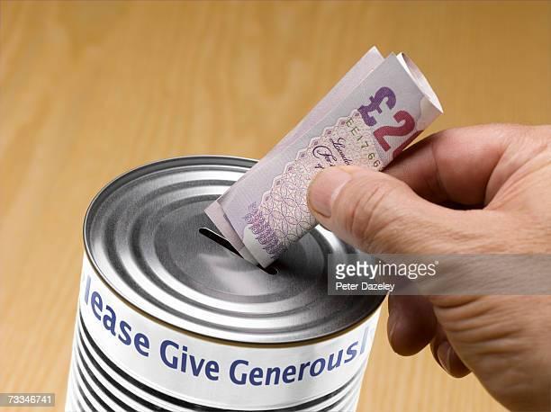 person putting twenty pound note into donation tin - twenty pound note ストックフォトと画像