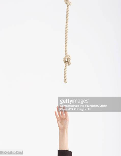 person reaching for rope suspended above, close-up of hand - cuerda fotografías e imágenes de stock