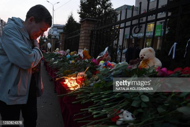 Person reacts at a makeshift memorial for victims of the shooting at School No. 175 in Kazan on May 11, 2021. - At least nine people, most of them...