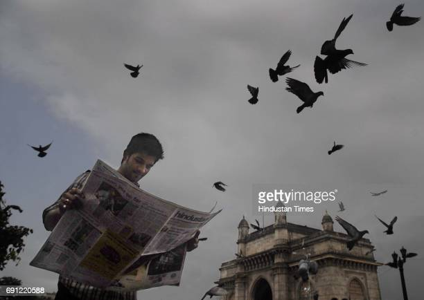A person reading a newspaper at the Gateway of India while the pigeons fly on a cloudy evening on Thursday