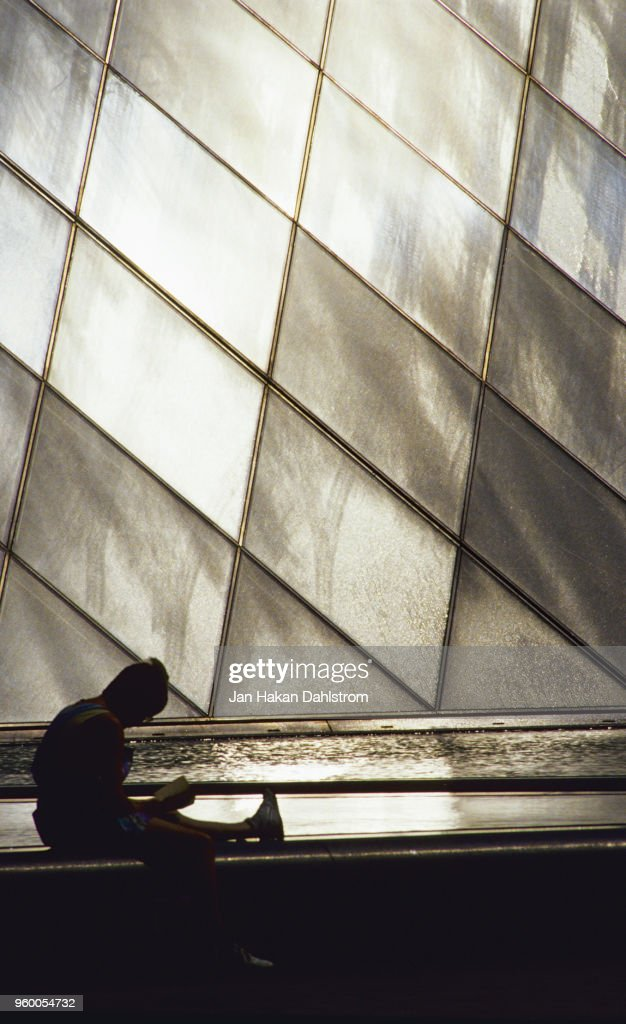 Person reading by the glass pyramid at the Louvre museum : Stock-Foto