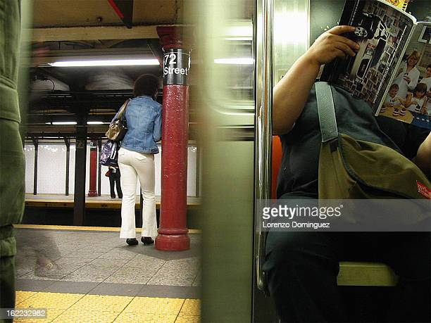 Person reading newspaper on New York City subway