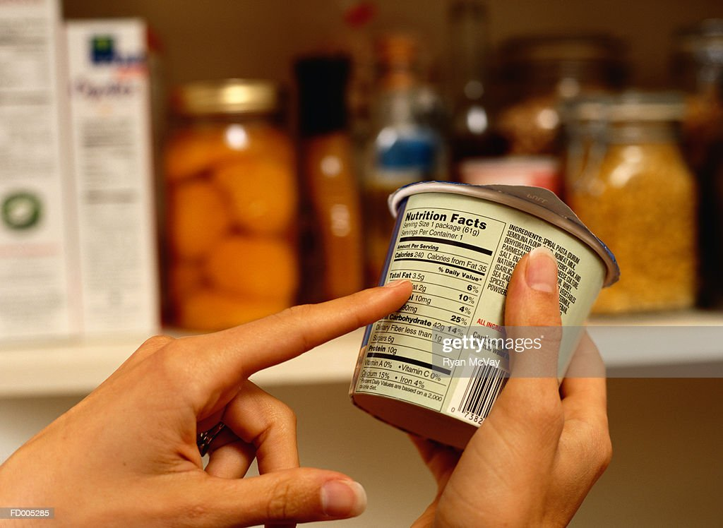 Person Reading Nutrition Label on Packaged Food : Stock Photo