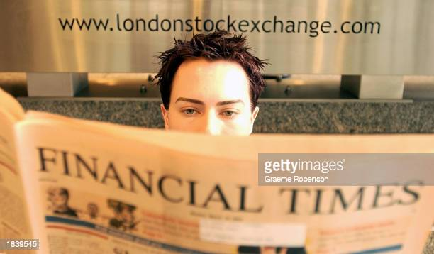 A person reads a copy of the 'Financial Times' newspaper at the London Stock Exchange March 10 2003 in London Midday share prices were down With the...