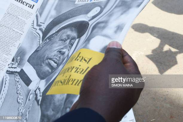 A person reads a newspaper article the death of former Kenya's president Daniel Arap Moi in Nairobi on February 4 2020