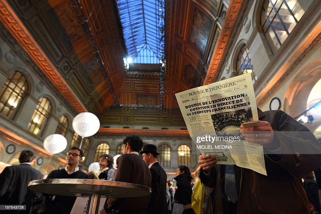A person reads a paper at the Palais Brongniard in Paris on December 4, 2012 during the launch of the first 'Innovation stock market' where 40 start-ups were symbolically quoted on the exchange. AFP PHOTO / Miguel MEDINA
