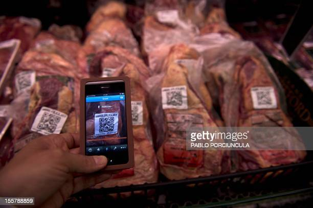 A person reads the QR code of Uruguayan beef at a supermarket in Montevideo on November 02 2012 The traceability of the meat which is mandatory in...