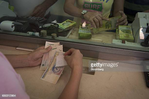 A person receives Pesos in exchange for Bolivars after the reopening of the borders in Cucuta Colombia on Tuesday Dec 20 2016 President Nicolas...