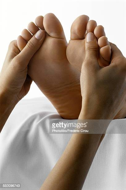 person receiving foot massage, close-up - foot massage stock pictures, royalty-free photos & images