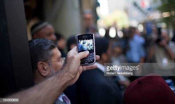 Person records on his Blackberry mobile device as leaders from various Muslim organizations hold a press conference in front of the proposed site of...