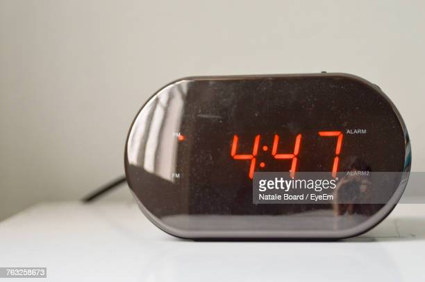 Person Reflecting On Digital Alarm Clock At Home