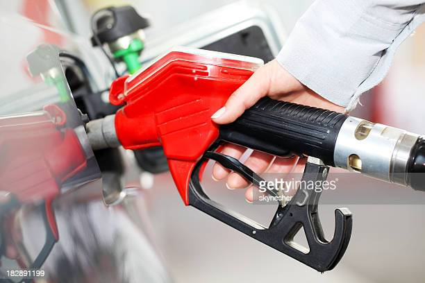 Person refueling a car at gas station.