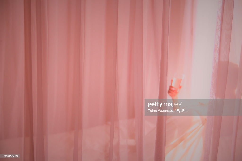 Person Relaxing Behind Pink Curtain Stock Photo