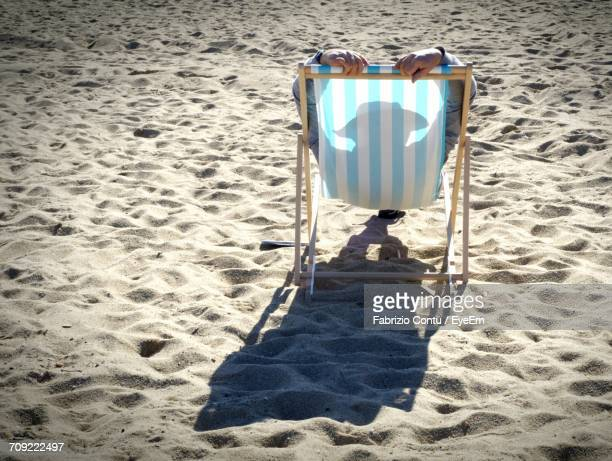 Person Relaxing In Deck Chair At Beach