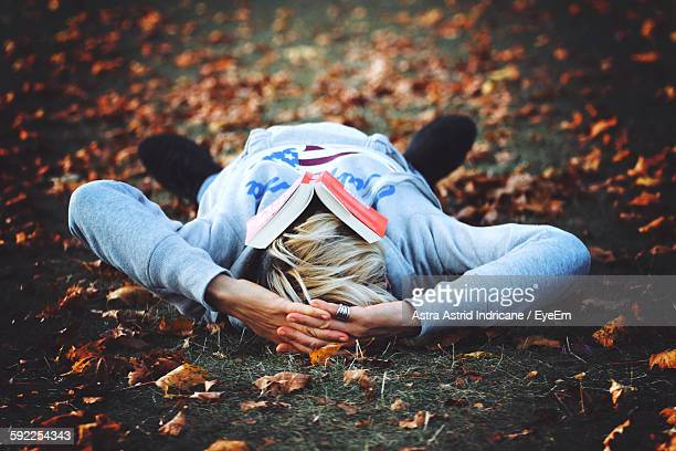 Person Relaxing On Field Surrounded By Leaves