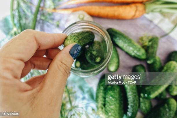 Person removing cucumbers from jar