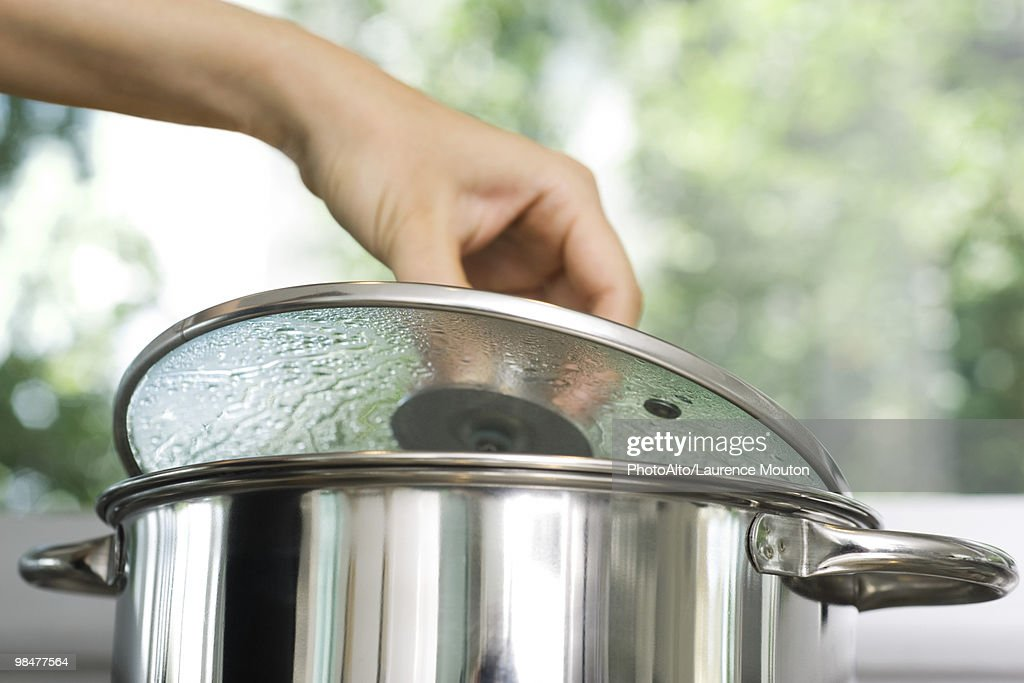 Person removing lid from cooking pot : ストックフォト