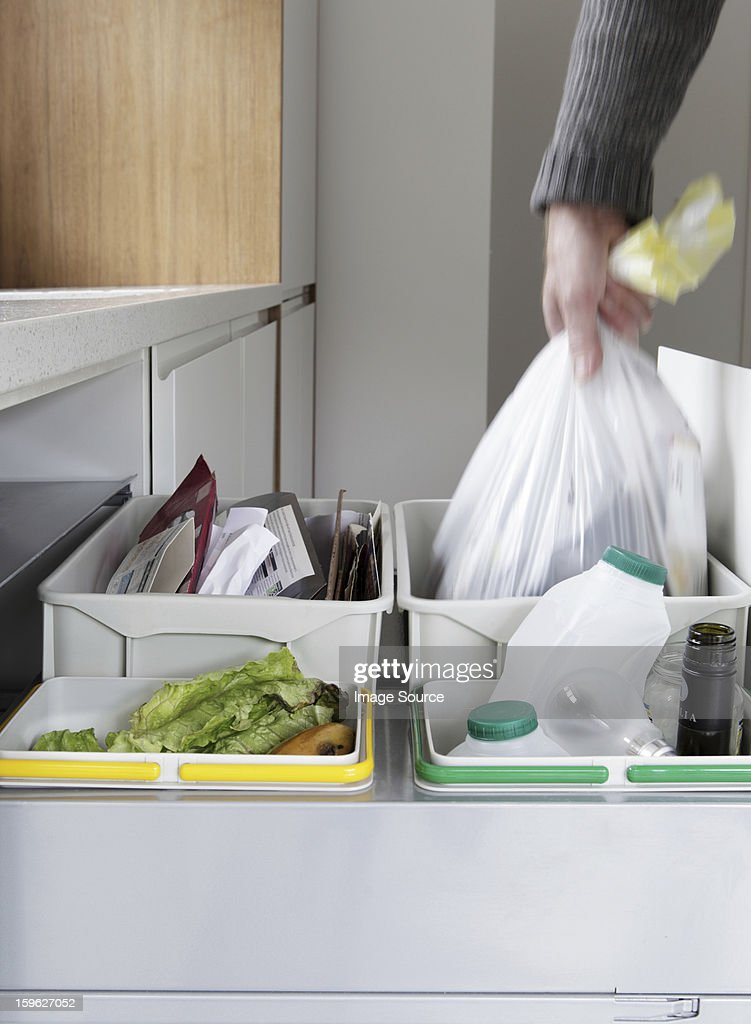 Person removing rubbish bag from waste and recycling drawer : Stock Photo