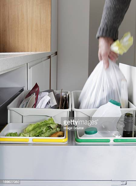 Person removing rubbish bag from waste and recycling drawer