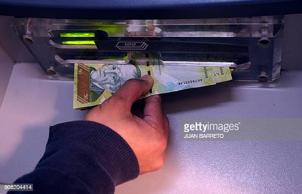 A person retires currency from a cash dispenser in Caracas on February 3 2106 In Venezuela there are no dollars but the economy of the country and...