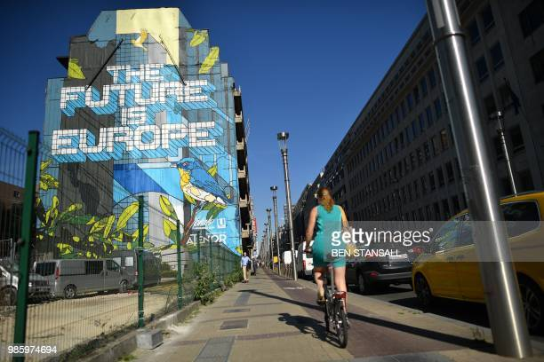 A person rides a bicycle along an art creation by Belgian street artist Julien Crevaels aka Novadead on June 28 2018 in Brussels / RESTRICTED TO...