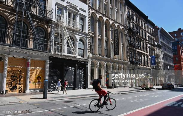 A person rides a bicycle past storefronts on Broadway in the SoHo neighborhood of Manhattan on June 24 2020 in New York City New York businesses...