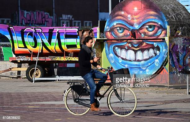 A person rides a bike in front of street artist's works at at the NDSM shipyards in Amsterdam on September 27 2016 / AFP / EMMANUEL DUNAND /...